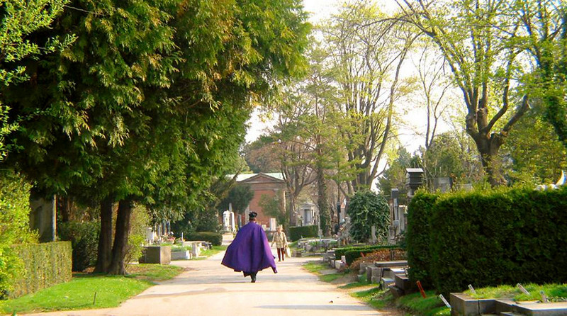 Priest, Central Cemetery, Vienna - Central Cemetery opened in 1874, and continues to serve Vienna's needs into the 21st Century. This priest, striding down the Cemetery's main avenue, has just left a funeral.