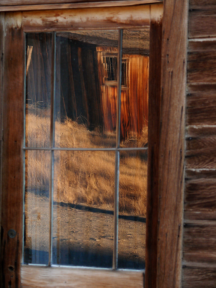 Dreamscape, Bodie - To capture the essence of a ruined town, I look for ways to abstract, imply, and symbolize, rather than merely describe its appearance. The 19th century window glass in many of Bodie's windows offers a perfect reflective surface for my purpose here. The old house reflected in the widow is split and dismembered. It almost seems to be moving between the panes in the window. Much of Bodie's charm rests in the domain of the human imagination. And so does my expressive purpose here. My viewers can take this picture of a reflection and make of it whatever they wish.
