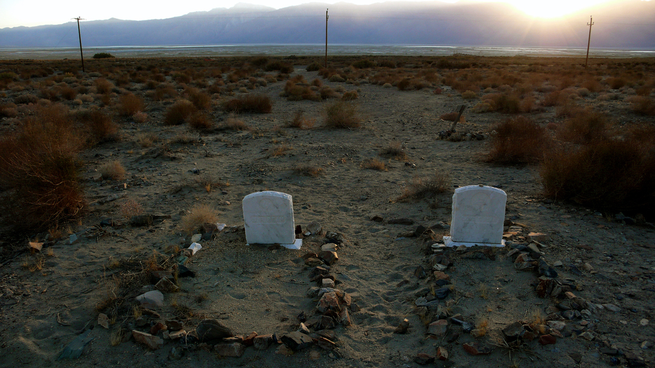 Cemetery, Keeler, California - The graves of a husband and wife rest on a hillside above the distant highway. Someone has taken the time and effort to border both graves with stones. In a way, these borders are more of memorial than the headstones themselves. They show that someone still cares. I made this image with a 28mm wideangle lens, shooting straight into a sun setting beyond the distant hills. A few seconds after I made this photograph, it was dark and we left the occupants of these graves to rest in peace.
