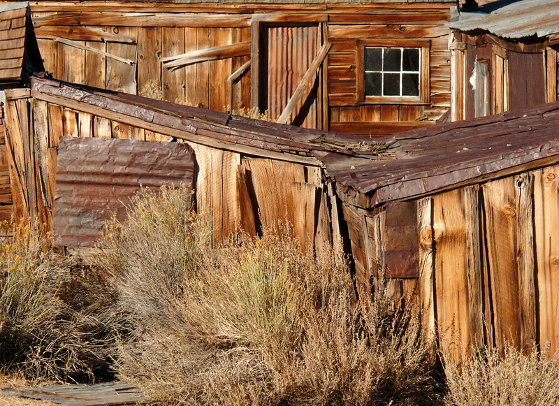 "Remnants of Bodie - In 1879, Bodie boasted a population of 8,500 people and more than 2,000 buildings. More than 60 saloons lined the streets of this booming California mining town high in the Sierras near the Nevada border. Gunfights, holdups and street brawls were common and created a wild atmosphere. It was a boom or bust town -- by 1881, only 1,500 people lived and work here. A fire all but wiped out the town in 1932, and by the 1940s, it was a ghost town. Today remnants such as these are preserved in a state of ""arrested decay"" -- a dead city, suspended in time."