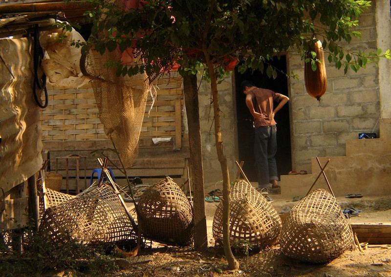 Taking a Break on the Farm - Hmong farm workers carry heavy baskets such as these on their backs. Day's end brings a welcome respite.