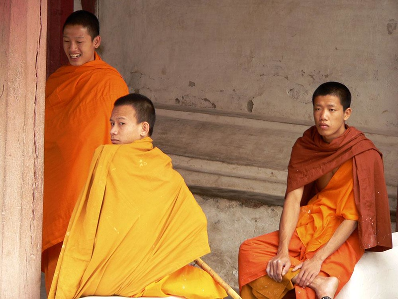 Three Monks at Luang Prabang - These monks seem well aware of the vivid colors their robes bring to this most beautiful of all Laotian towns.