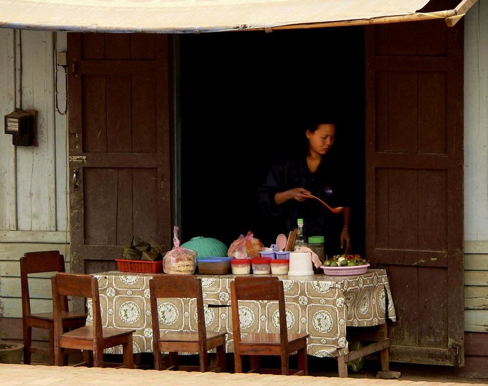 Woman with ladle, Luang Prabang - Luang Prabang is a place that lives in the past as well as the present. This woman, poised with her ladle over a serving table at a street-side restaurant, may just as well have been standing here with ladle in hand 100 years ago