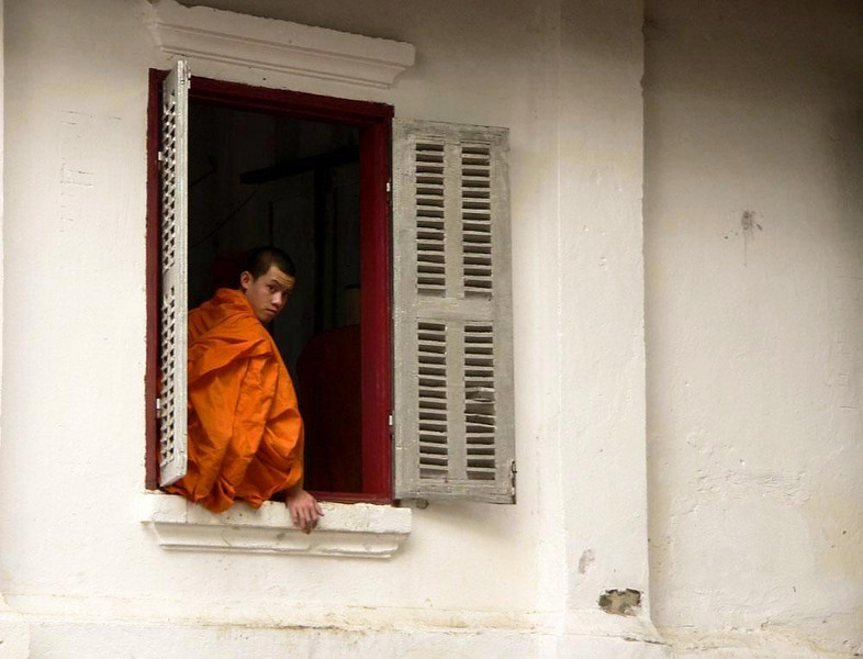 Cloister window, Luang Prabang - A monk gets a long view of the world from his monastery window in Luang Prabang.