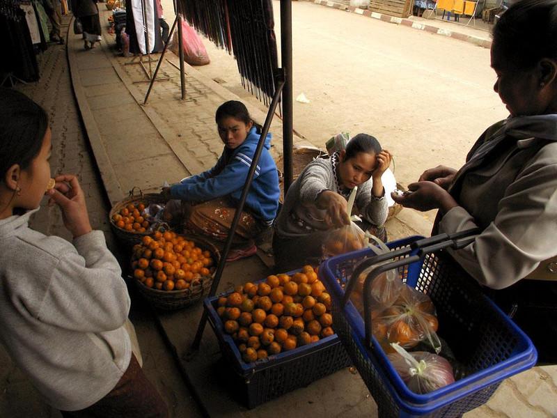 Tangerines, Luang Prabang market - Shoppers sample the tangerines at Luang Prabang's colorful produce market.