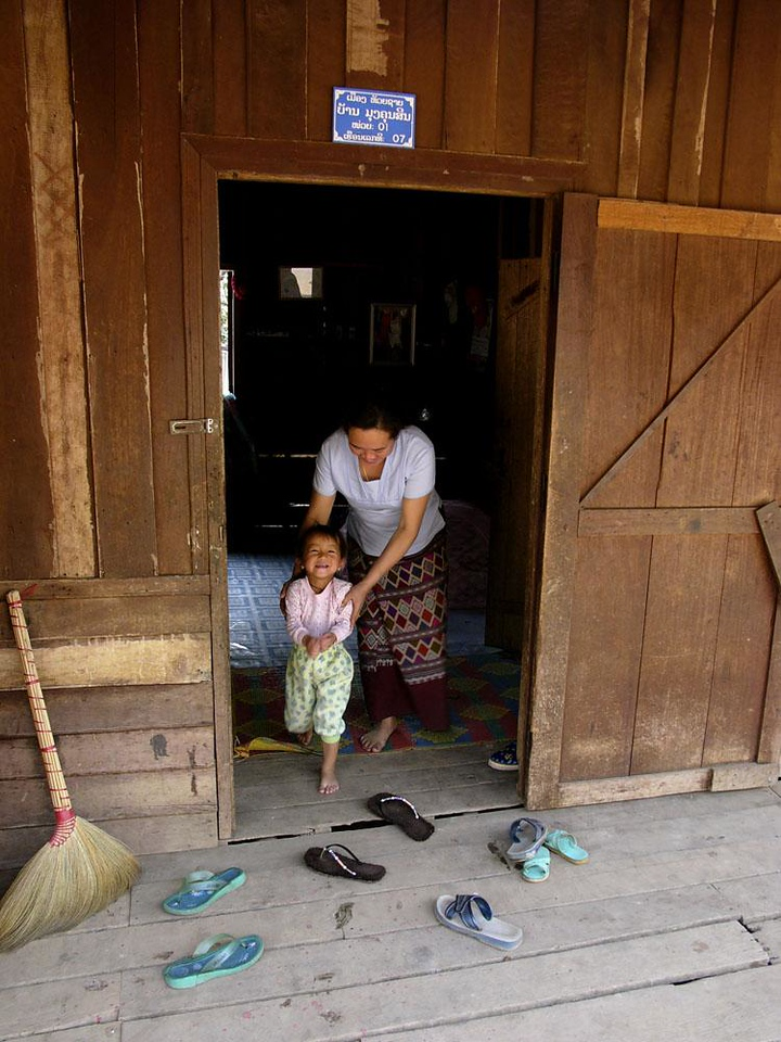 A Lao welcome - As I passed this village house, a woman encouraged her young son to warmly greet us. He did.