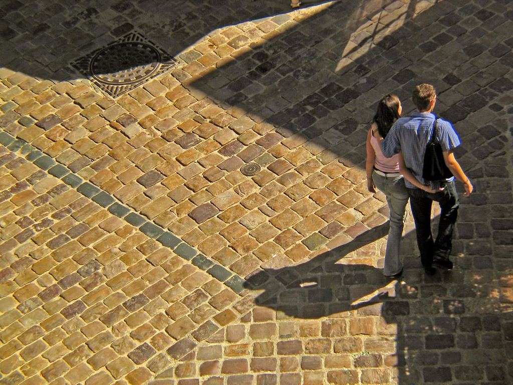 Friends, St Malo - I made this photograph from the ramparts because of the play of light and shadow on the cobblestone street, the patterns of the cobblestones themselves, and the young man and woman who walk through the old city together as if they are one.