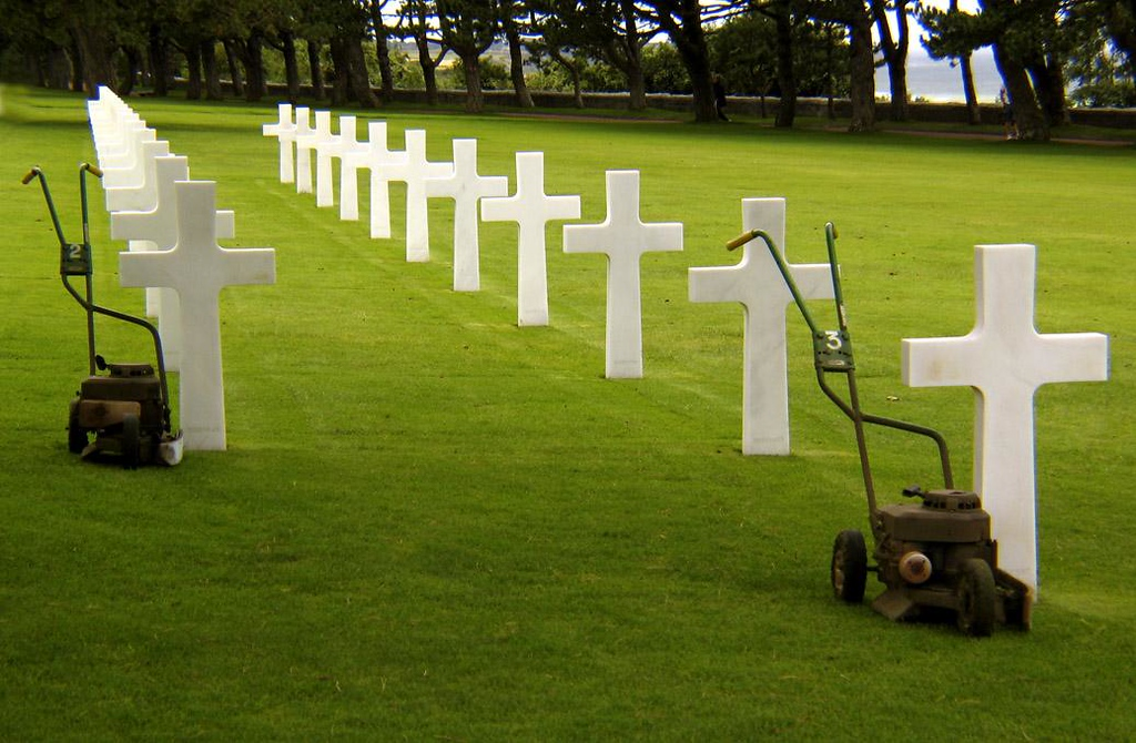 At ease, US Cemetery, Omaha Beach - Lawn cutters on break align their numbered military mowers precisely next to the first graves in each row. Nothing is left to chance. The cemetery's 72 acres are a virtual green carpet.