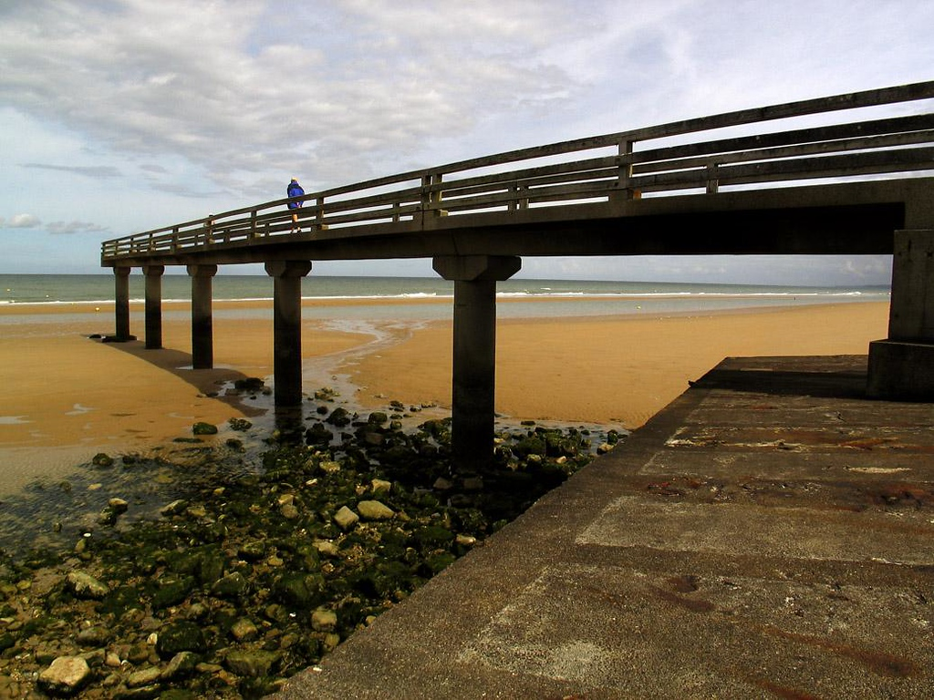 Ebbtide, Omaha Beach, near St. Laurent - A fishing pier is left high and dry at ebbtide on Omaha Beach. One end of the pier is anchored to a cement caisson which was once part of an artificial harbor that played a critical role on D-Day.
