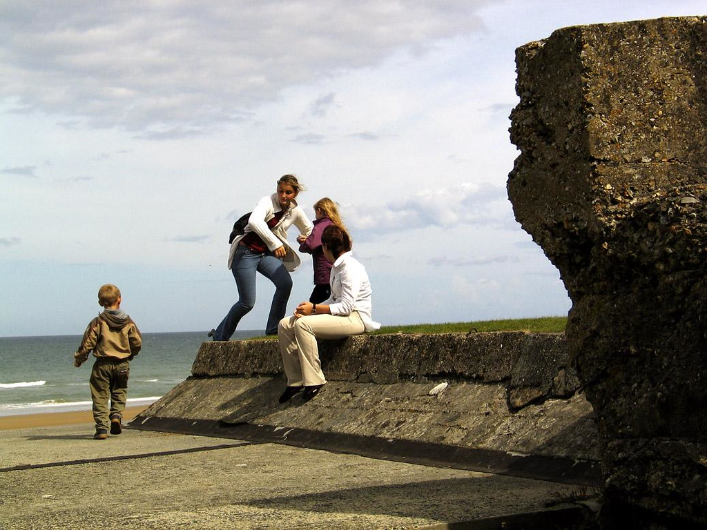 At play on the ruins of war, Omaha Beach - The Allies towed and sunk cement caissons for a second artificial harbor, which was installed at Omaha Beach near the village of St. Laurent. Today children play on the remnants of those massive caissons.