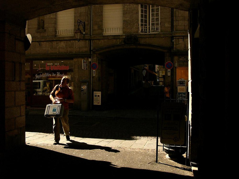 """Technician, St. Malo - I was lurking inside of an archway, focusing my camera on a patch of sunlight in the street and waiting for someone to walk into my picture. A lot of folks came by, but none seemed as intense as this fellow who looks like a technician in search of his customer. It was the last shot I would make in France -- my ship was about to sail. To move on to the third and final article of this three part series on European ports, go to: <a href=""""http://www.worldisround.com/articles/75601/index.html"""">http://www.worldisround.com/articles/75601/index.html</a>"""