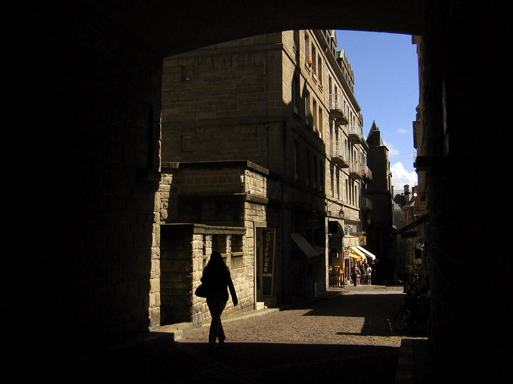 On the streets of St. Malo - St. Malo offers a maze of ancient streets, which often run through archways cut into buildings. The afternoon sun creates striking shadows that play across the face of St. Malo's buildings and along its cobblestone streets.