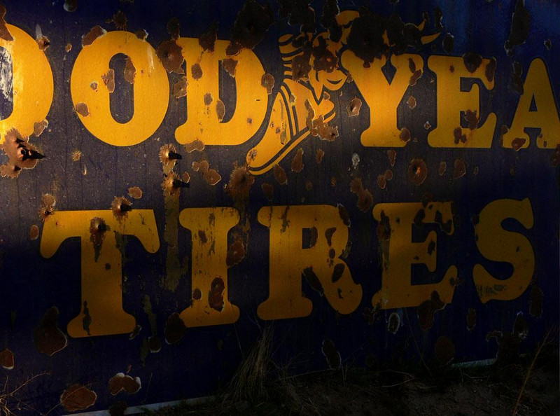 Tire sign - This sign is still another relic that may well have once announced its product alongside of US Route 66. Today, pock marked with bullet holes, it rusts away in the front yard of Tom's Welding and Machine Shop in Barstow.