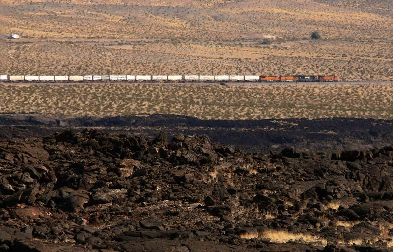 The Mohave from Pisgah Crater, Ludlow - Pisgah Crater is a lava flow in the Mohave Desert, the residue of a volcano that last erupted about 2,000 years ago. I stood at the base of its cider cone and photographed a freight train crawling across the desert floor in the distance.