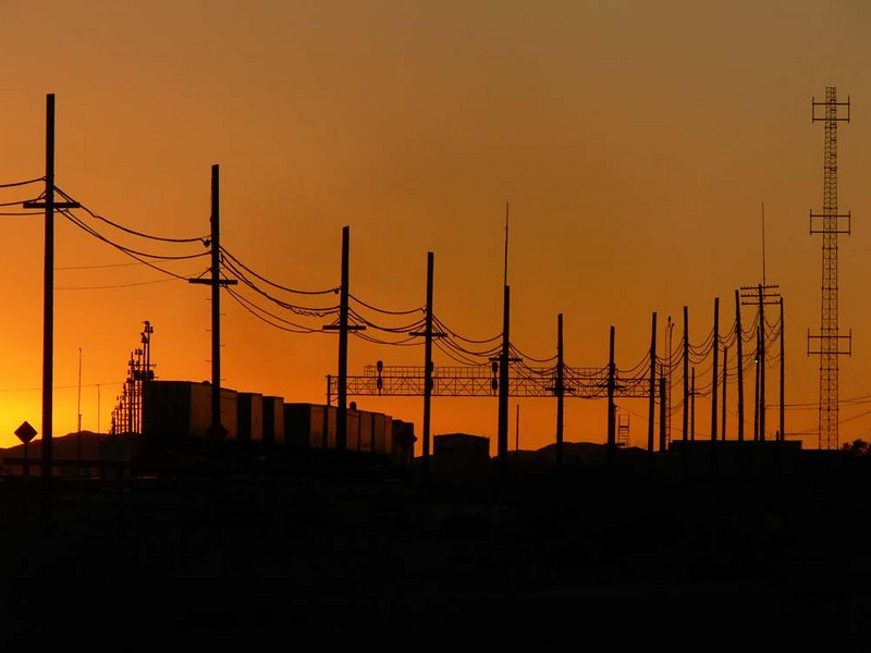 Freight Train, Barstow - The powerlines provide the stage, the setting sun the backdrop, and the freight train is the principal player in this Barstow scene.
