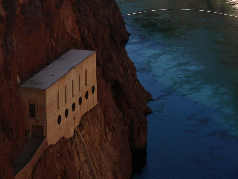 Valve House, Hoover Dam - The deep blue waters of Lake Mead flow beneath one of two valve house set into the cliffs flanking Hoover Dam. The equipment in these houses can move water around the dam in case of an emergency or flood.