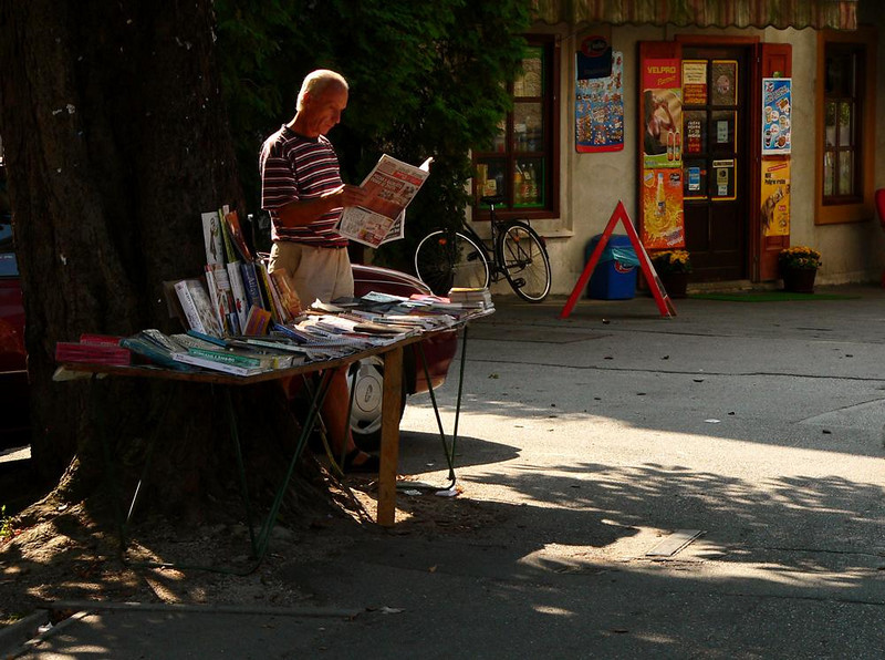 Newsstand, Samobor - When this newspaper paper is not selling his wares, he is reading them.