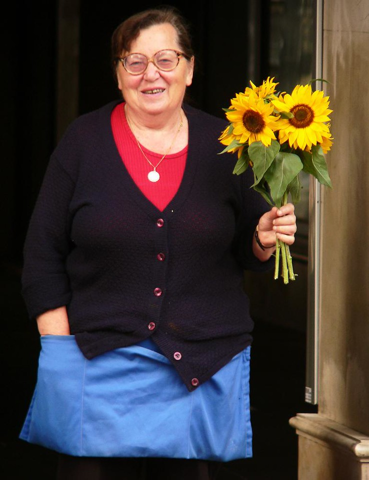 Dolac Flower Market, Zagreb - This Sunflower vendor was delighted to find my camera aimed her way. I chose her because she presents us with the three primary colors -- red, blue, and yellow.