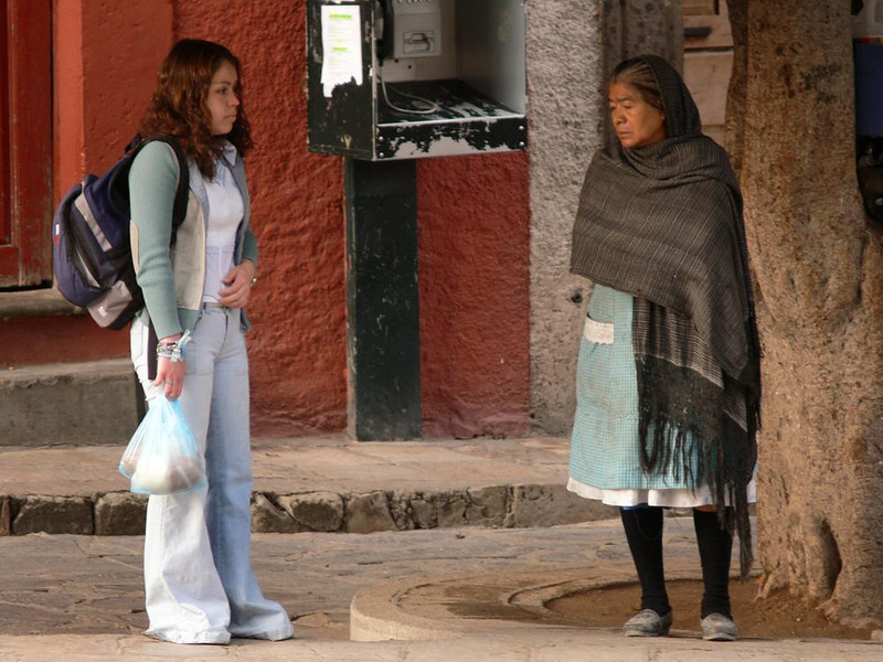 Two worlds of San Miguel - In San Miguel, as in other parts of Mexico, there is often a striking contrast of life-styles between the young and the old. These women were waiting at a bus stop, looking at each other in absolute silence.
