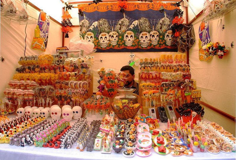 Day of the Dead Sweets - Mexico celebrates both Halloween and the Day of the Dead, a holiday honoring the spirits of those no longer with us. This booth, set up in a Guanajuato plaza, offers treats for both holidays. The proprietor hides from the camera, using a batch of pumpkins as a makeshift mask.