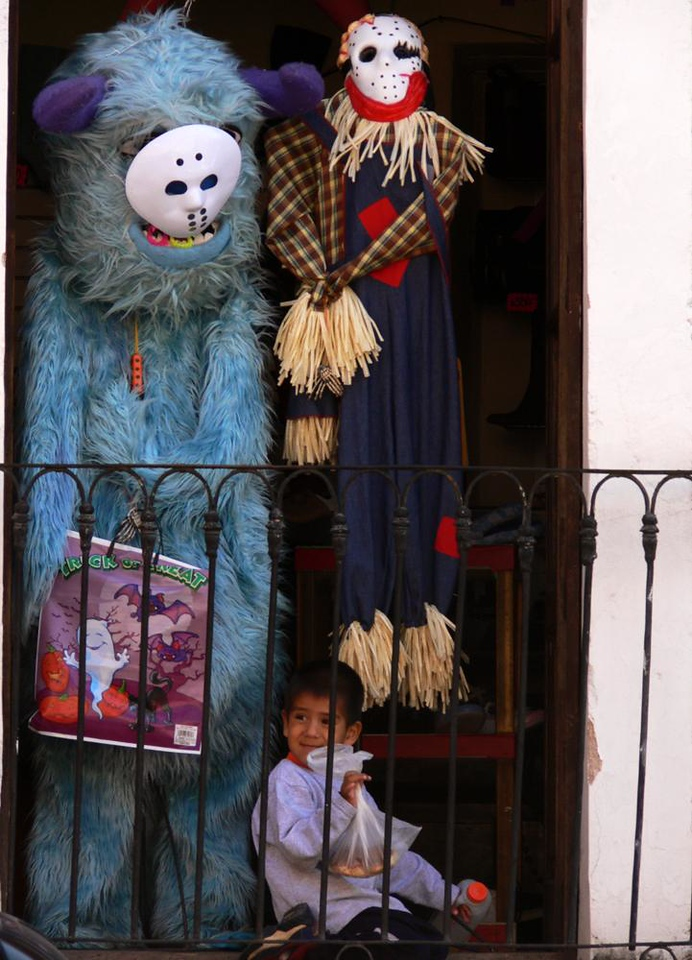 Holiday Dreams - A child plays in the shadow of monstrous figures decorating his home. It was just a few days before Halloween and The Day of the Dead holidays.