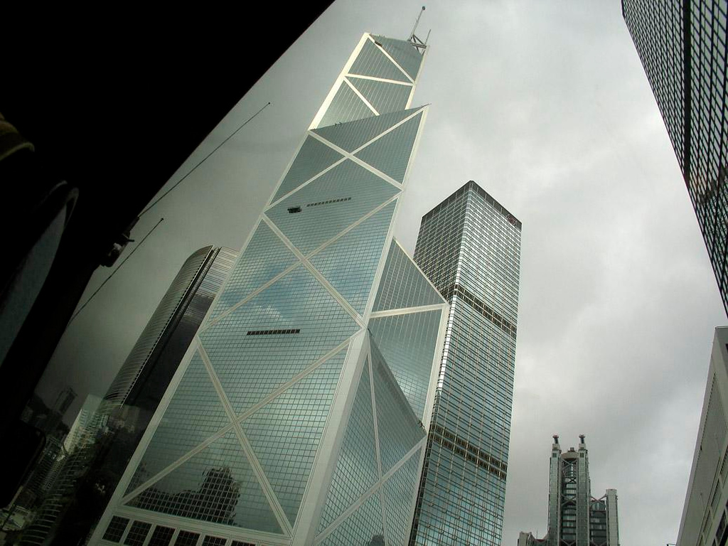"View from the bus, Hong Kong Central - I.M. Pei's Bank of China dominates a skyline that has few rivals in China. Only Shanghai's new Pudong district is comparable. I shot this film on a gray morning from the window of a moving bus. It is virtually a black and white image, but for the tinge of color reflected back to us in the Bank of China's windows. The building's sharp angles point at other banks, which is said to create bad ""feng shui."""