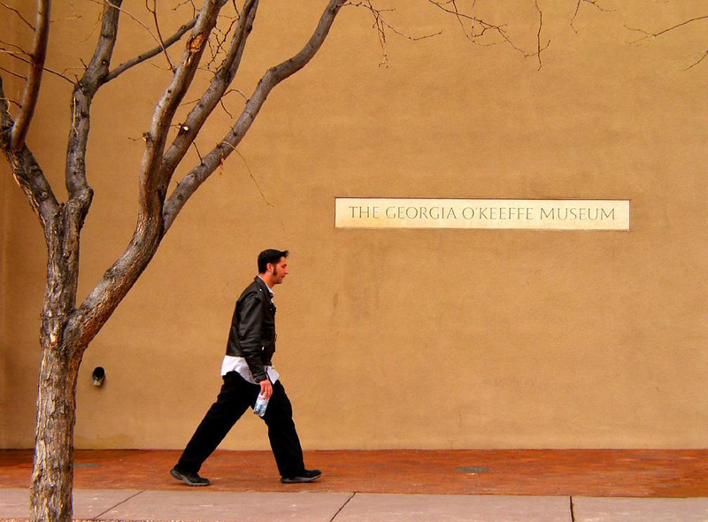 On the move in Santa Fe - A lone pedestrian moves past the new Georgia O'Keefe Museum in downtown Santa Fe. (I waited for this fellow to enter my frame -- his lean perfectly repeats the thrust of that tree's branch.)
