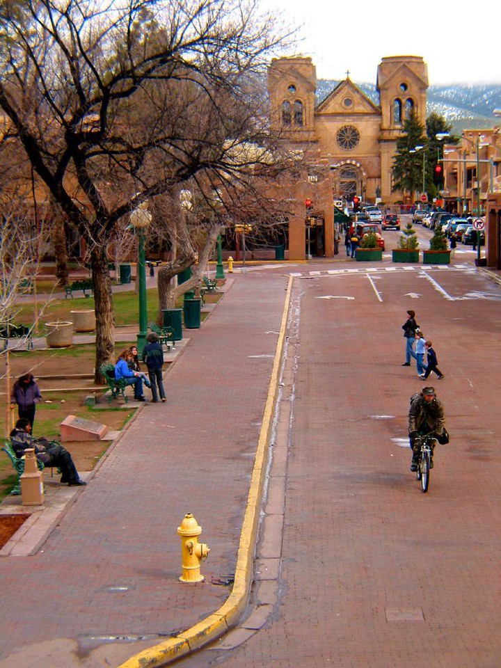 On San Francisco Street, Santa Fe - I shot this street scene along Santa Fe's plaza from the dining balcony of a restaurant. In the distance rises St. Francis Cathedral.