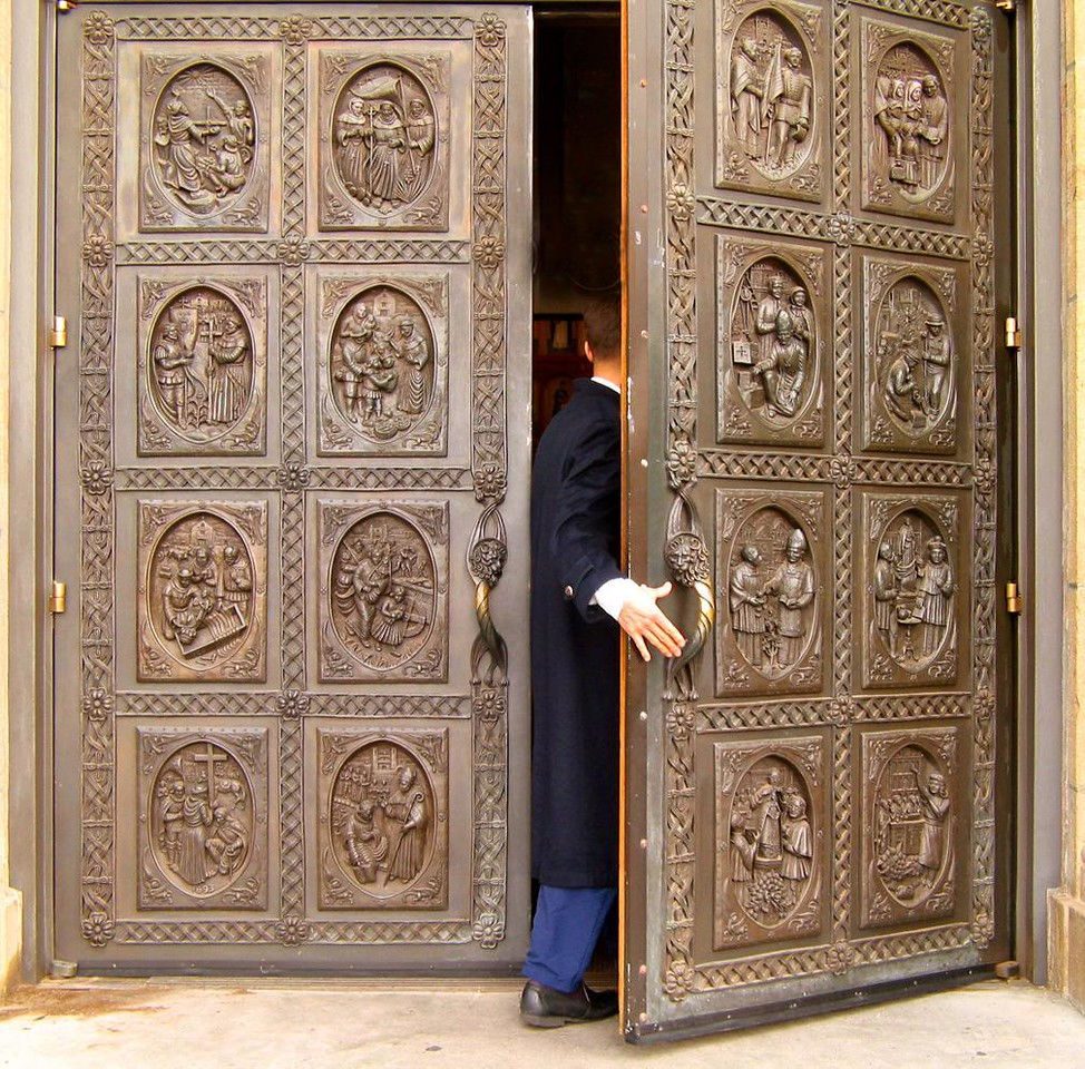 Old doors and an injured hand - As I was photographing the ornate bronze doors of Santa Fe's St. Francis Cathedral, a young priest hurried past me and entered the building. I photographed him as he disappeared within, leaving only a bandaged hand behind for us to wonder about.