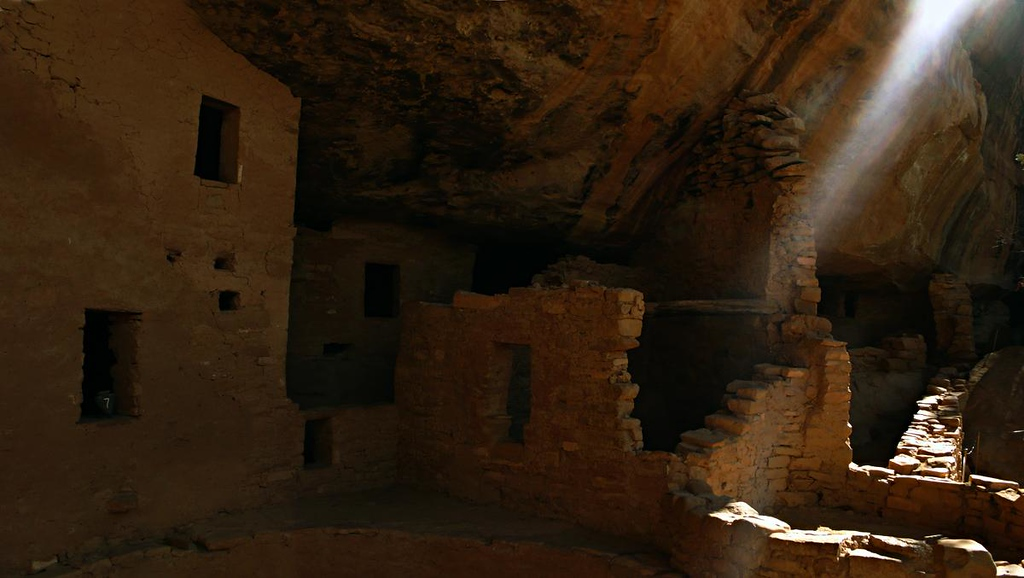 Ancient cliff house, Mesa Verde - A shaft of light grazes the ruins of Mesa Verde's Spruce Tree House, a cliff dwelling built during the 11th century. It had more than 100 rooms, and is in excellent condition because it is protected from weather by an overhanging cliff.