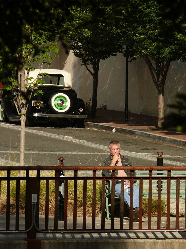On the Petaluma River - Time seems to stand still in Petaluma. The great earthquakes that rocked the Bay area in the 20th century spared this town. With old buildings and a vintage car behind him, this man takes his coffee down to the Petaluma River to muse on times gone by.