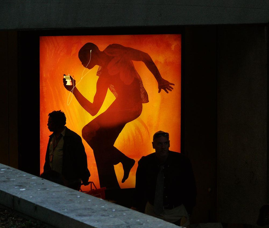 San Francisco commuters - Hundreds of Bay Area Rapid Transit commuters enter San Francisco by passing under an illuminated iPod ad. Few seem to notice it.