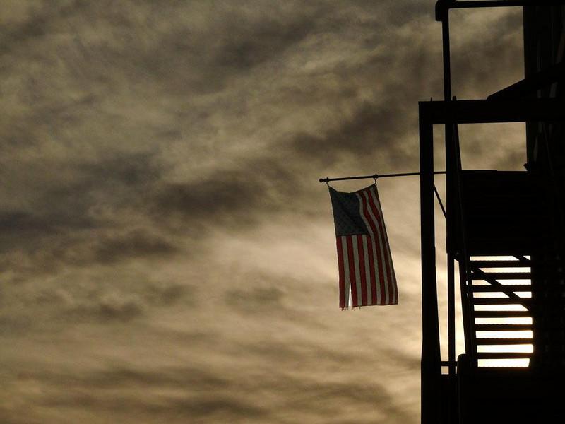 Dawn colors, Petaluma - An old fire escape, a tattered flag, and a cloud laden sky greet the new day in Petaluma, California.