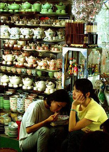 Soup break, Ho Chi Minh City, Vietnam - I like the body language of these sales people in Ho Chi Minh City's central market. Rows and rows of teapots add context. My digital camera allows me to work without using a flash. My subjects never noticed me.