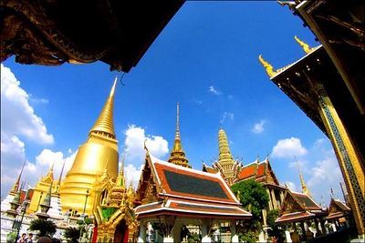 Grand Palace, Bangkok, Thailand - Bangkok's Grand Palace is one of the most spectacular attractions in the world. The buildings reflect many styles and purposes. To play them against each other, I used a wideangle lens attachment, which changed the wideangle end of my zoom lens from 28mm to 17mm. Although this view is slightly distorted, I felt the tilted buildings gave this surreal place a dream-like appearance.