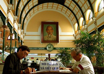 Post Office, Ho Chi Minh City, Vietnam - The old Siagon post office, with its soaring ceiling, dates from the French colonial era. Today it is the communications center for Ho Chi Minh Citys residents. I found these men hard at work under the ever present gaze of Ho Chi Minh.