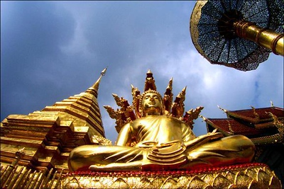 Buddhist temple, Chiang Mai, Thailand - I used the wideangle attachment on the wide end of my zoom lens to help me pull the golden spire, the statue, and the towering umbrella together from a low angle. Using a digital camera, I was able to make the shot over and over, shifting my position slightly after each exposure, until I was sure that everything was where I wanted it to be. The result: an image from another world.