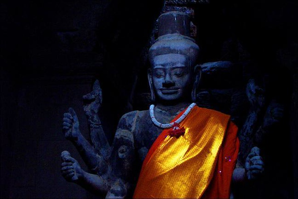 Hindu God Shiva, Angkor Wat, Cambodia - I took this shot without flash, using the light from a distant doorway. The bright orange Buddhist robe reflected that light into my camera, while the black statue, stained by twelve centuries of incense, fades into the background. (This photo is also the cover shot of my album. To me, it most strikingly represents the eternal mystery of Indochina.)