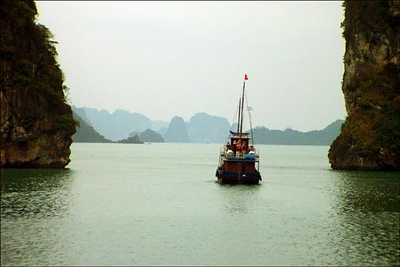 Sailing on Halong Bay, Vietnam - The principal attraction of Halong Bay is the sight of hundreds of strange, rocky islands looming ahead. I waited until the boat ahead of us created a pictorial focal point, and only then did I make this shot of the islands themselves.