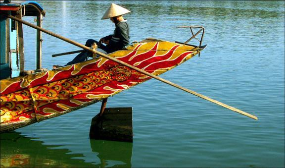 Boatman, Hue, Vietnam - The colorful boat, the long diagonal pole, the shimmering reflection of boat and rudder in the water, creat a perfect setting for this boatman at rest.