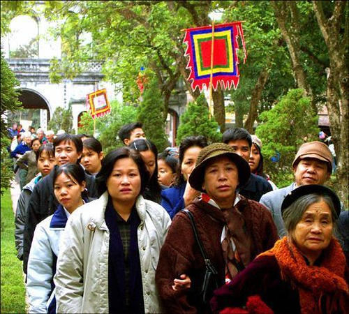 Tet visitors, Hanoi, Vietnam - Masses of visitors throng Hanoi's Temple of Literature at Tet, the Chinese New Year. Using a telephoto zoom lens, I photographed this crowd walking past a colorful banner. The long lens makes those in the foreground sharper than those in the background, simplifying an otherwise complex image. To me, these faces offer a mosaic of Vietnam.