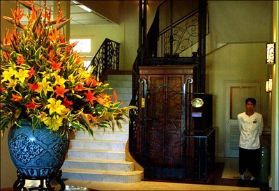 """Grand Hotel Angkor, Cambodia - I made this shot in the lobby, using window light. I thought the old """"lift"""" and adjacent bellman fit well with the vase of flowers. The hotel was built during the French rule of Cambodia, and a sense of that time still lingers here."""