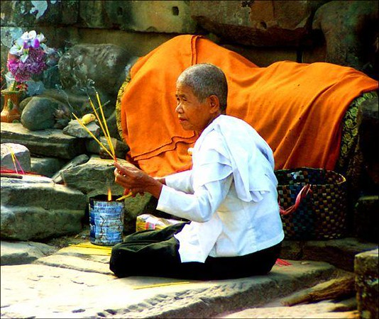 Offering, Angkor Thom, Cambodia - Pilgrims still make offerings at the ancient temples of Angkor. I photographed a woman selliing incense in The Bayon. Behind her, virtually unnoticed and wearing a Buddhist cloak, is a reclining statue of a Hindu God.