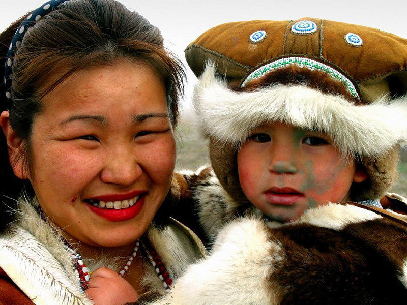 Chukchi portrait, Mainapilgino - This Chukchi woman has dressed her young son in furs, and painted his face to celebrate our visit to her village. He won't let go of her necklace.