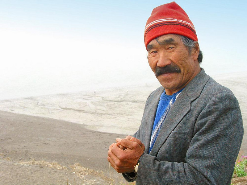 Siberian gentleman, Mainapilgino - I found this man standing alone on a bluff overlooking the Bering Sea at Mainapilgino. I showed him my camera and asked if I could make his picture. He smiled, and hands folded, he patiently stood before me with great dignity while I made a number of photographs. His hair flows out of a red knit hat. He wears a sport jacket, a blue sweater, and a wrist watch. Who is he? How has he made his livelihood? Good pictures usually offer more questions than answers.