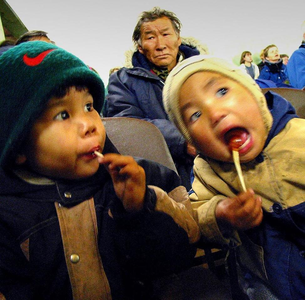 Koryak kids, Tymlat Bay - Two Koryak kids enjoy candy from America at Tymlat Bay's cultural hall.