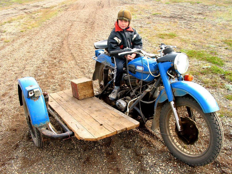 Young boy on a motorcycle, Mainapilgino - I found this solemn young Siberian boy seated on an old motorcycle fitted with storage platform instead of a second seat. He patiently sat for his portrait without ever moving or smiling. What he could be thinking?