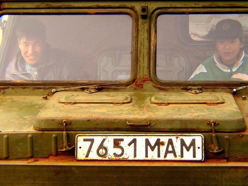 Boys in the window, Mainapilgino - Old military vehicles are common in Siberian villages where roads are rough or non-existant. Here two Kamchatkan boys enjoy the festivities through the window of an old half-track,
