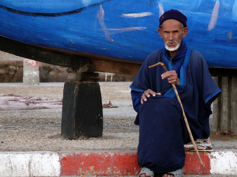 At the port, Essaouira - The blue garments on this man match the old boat behind him. Blue is the prevailing color in Essaouira's harbor.