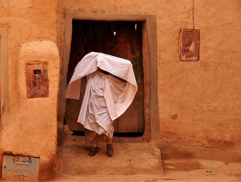 Veiling, Tineghir - While walking through Tineghir's medina, I saw this woman veiling herself in front of a house.